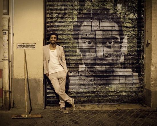 """Patrice vor dem Artwork seines neuen Albums """"One"""". Bild: www.patrice.net"""